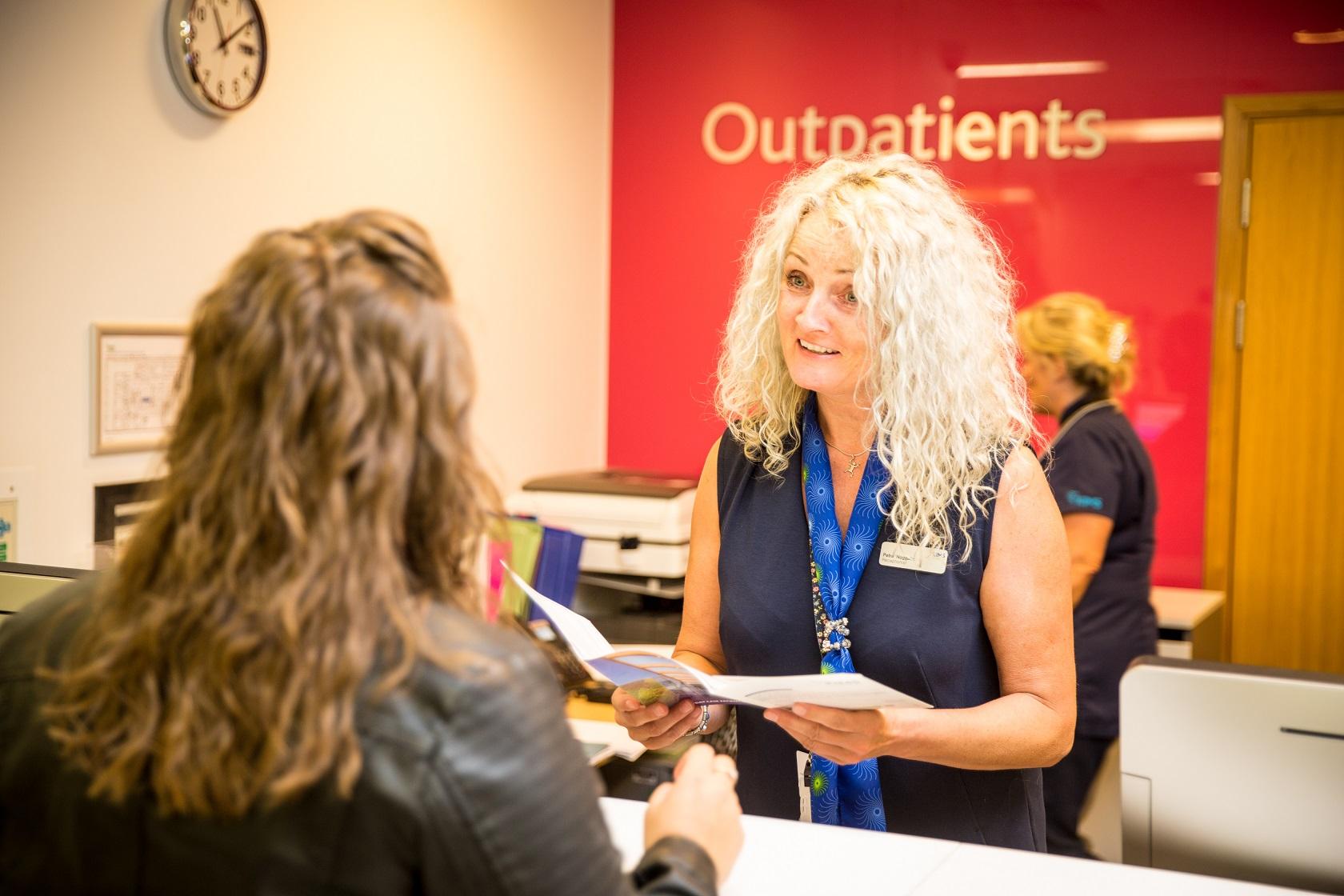 patient at reception desk in outpatients