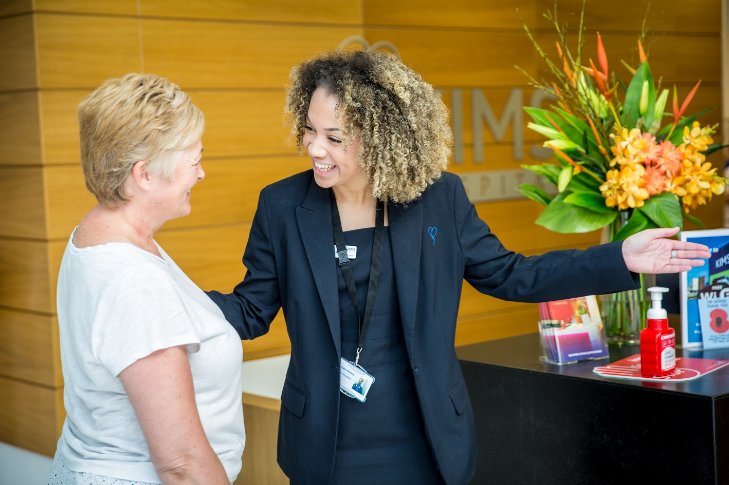 receptionist greeting patient at KIMS Hospital main entrance