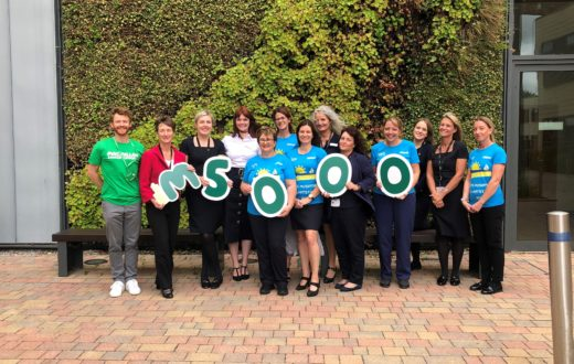 KIMS Hospital team outside the living wall celebrating raising money for macmillan
